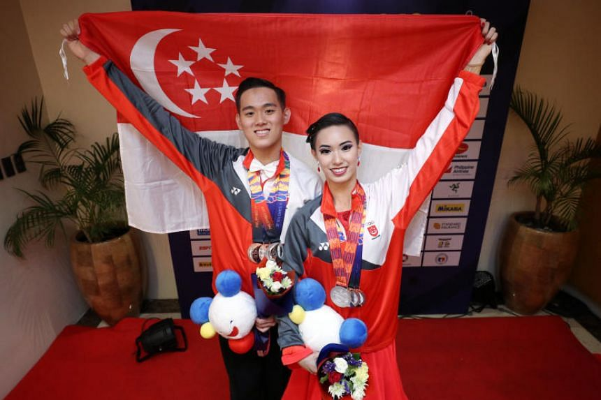 Singapore siblings Jerome and Rachel Teo posing with the national flag and their medals at the SEA Games on Dec 1, 2019.