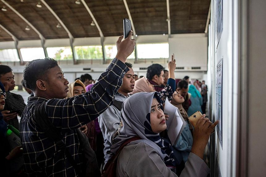 """Indonesian job seekers at a job fair in Surabaya in September. Indonesia will coalesce overlapping parts of 74 laws into one """"job creation law"""" that will go before Parliament in January, President Joko Widodo announced on Thursday."""