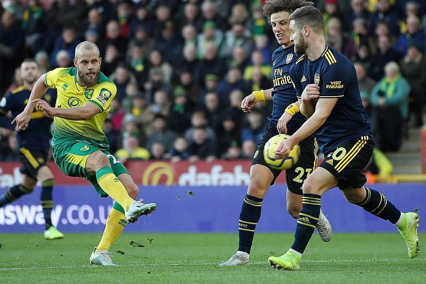 Norwich's Finnish striker Teemu Pukki dispatching a shot past his Arsenal markers David Luiz and Shkodran Mustafi to open the scoring for the home side.