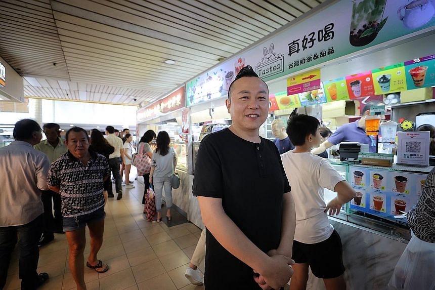 Mr Dai Heng Jiang beside his bubble tea stall and Sichuan cooked food stall (back) outside People's Park Complex in Chinatown. The Sichuan native, who is a permanent resident here, imports ingredients from Sichuan every month and counts as his custom