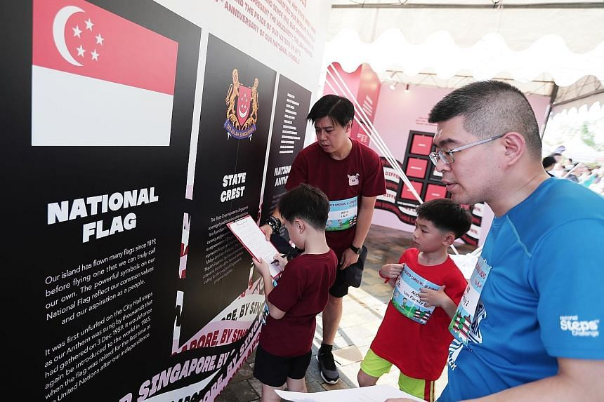 Families trying out quizzes that commemorate the 60th anniversary of Singapore's national symbols - the national flag, state crest and National Anthem - at the One Community Fiesta family sports carnival held at Jurong Lake Gardens yesterday. ST PHOT