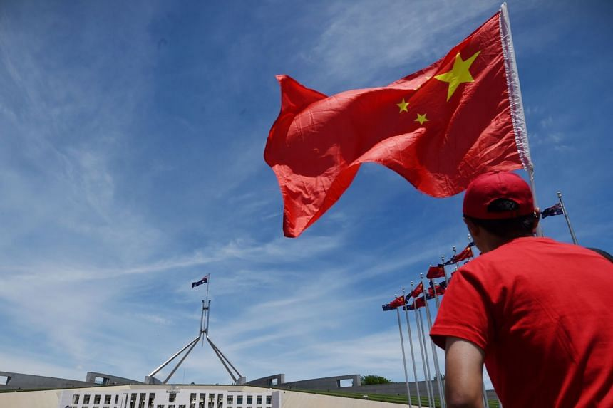In a photo from Nov 17, 2014, a Chinese government supporter waves a Chinese flag outside Parliament House in Canberra, Australia.