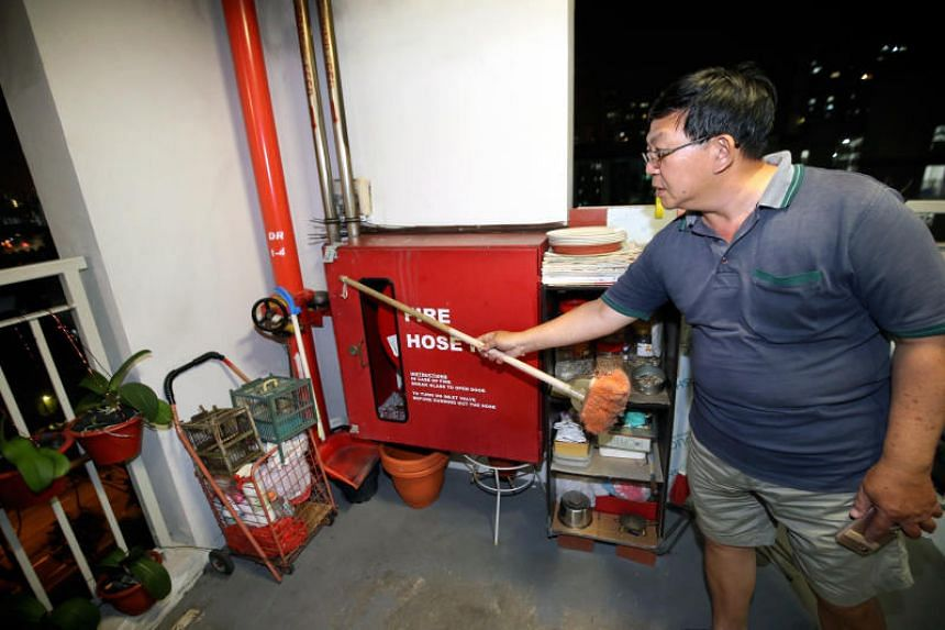 A resident pointing out the lock on the fire hosereel at Block 210A Bukit Batok St 21, on Nov 2, 2019.
