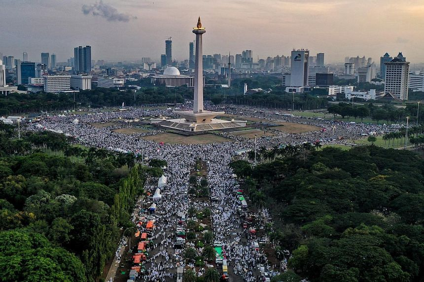 Thousands of people, many wearing white and carrying Islamic flags, took part in a peaceful rally in central Jakarta yesterday. The crowd began gathering for prayers at Jakarta's National Monument from about 3am, as more than 6,000 security forces, i