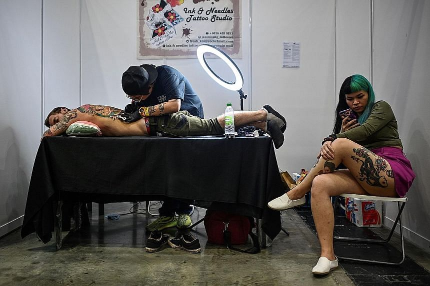 A tattoo artist working on a client during the Tattoo Malaysia Expo in Kuala Lumpur last Friday. The event was supported by Malaysia's Ministry of Tourism, Arts and Culture, according to the organiser's website. PHOTO: AGENCE FRANCE-PRESSE