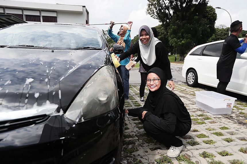 (From front to back) Sara Syaakirah, 15; Nur Amirah Aziz, 18; and Ms Rahayu Buang (in blue), chief executive of Yayasan Mendaki, were among the close to 50 youngsters and volunteers turned car washers on Sunday at a charity car wash event held at Men