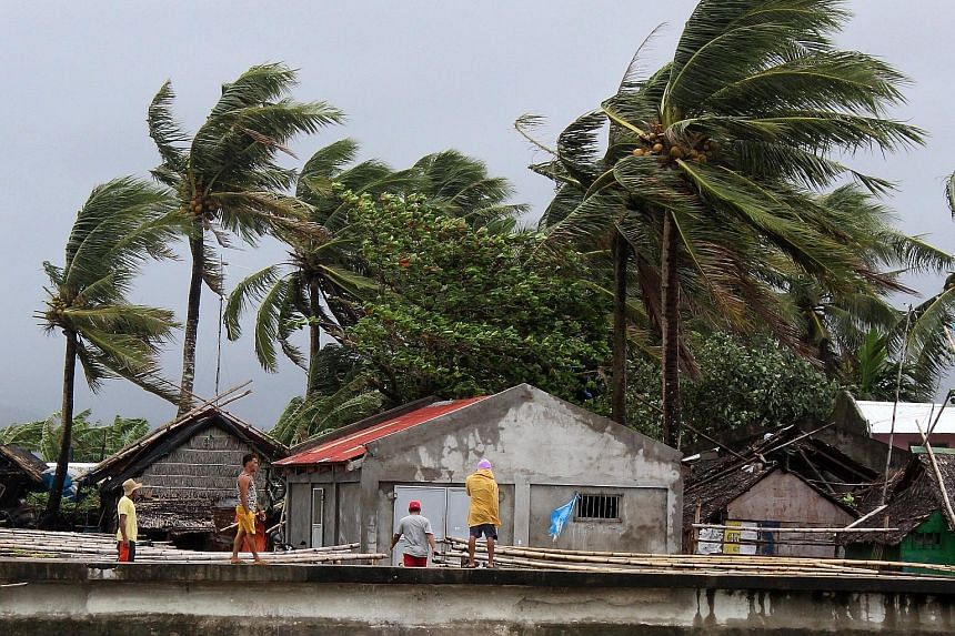 Strong winds blowing in the town of Calabanga in the Philippines' Camarines Sur province yesterday. Above: Filipino villagers getting off a truck as they evacuated their homes on Sunday in anticipation of the storm in Lagonoy town in Camarines Sur pr