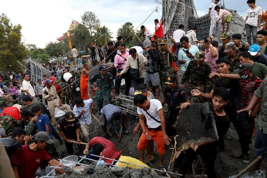 Cambodian rescuers search for victims from the collapse construction site in a Buddhist temple in Siem Reap on Dec 2, 2019.
