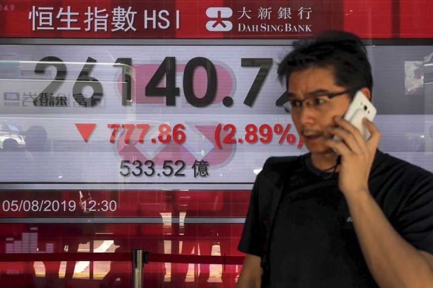 In the photo taken on Aug 5, 2019, a man using his smartphone walks by an electronic board showing the Hong Kong composite index outside a bank in Hong Kong.
