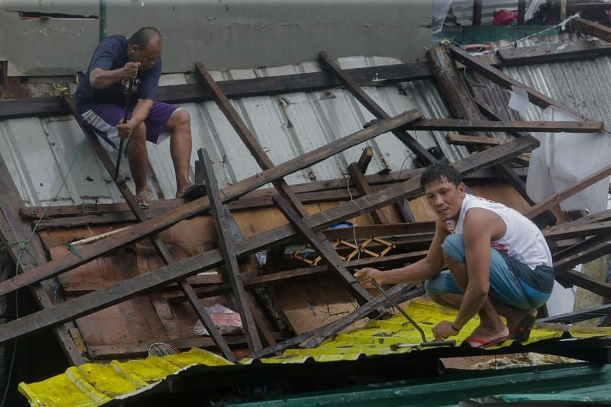 Residents repair their damaged houses after Typhoon Kammuri hit Legazpi City, Albay, on Dec 2, 2019.