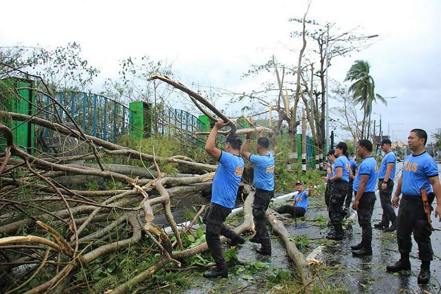 Policemen clear a road with fallen trees near the airport Legaspi City, Albay province, south of Manila, on Dec 3, 2019, after Typhoon Kamurri battered the province.