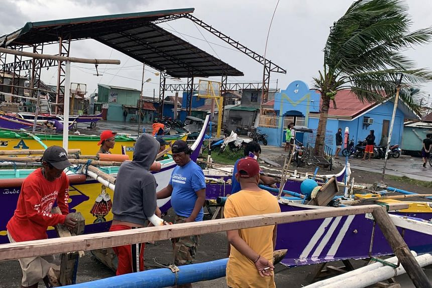 Fishermen secure boats in anticipation rain and strong winds brought by Typhoon Kammuri, in Cavite City on Dec 3, 2019.