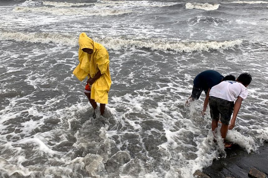 Villagers collect shells during strong winds brought by Typhoon Kammuri, in Cavite City on Dec 3, 2019.