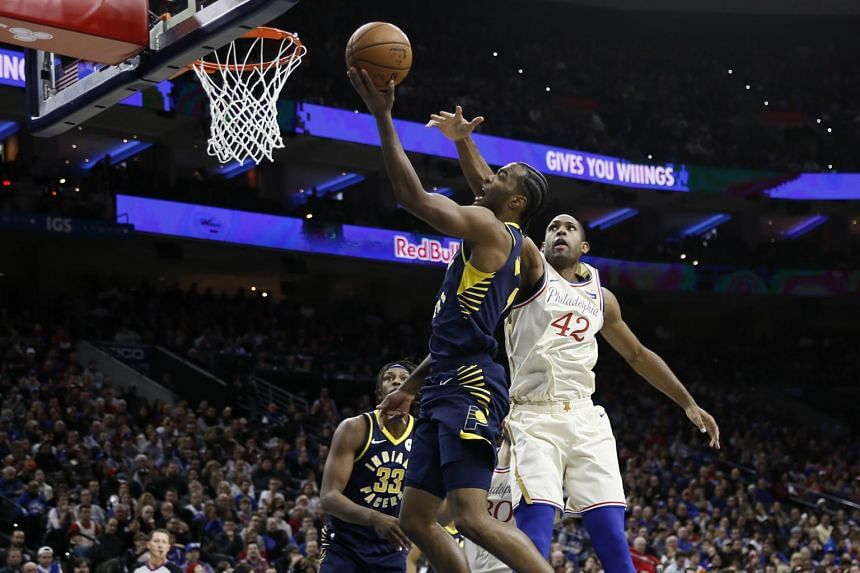 Indiana Pacers' T.J. Warren (centre) goes up for a shot against Philadelphia 76ers' Al Horford during the first half of an NBA basketball game, on Nov 30, 2019, in Philadelphia.