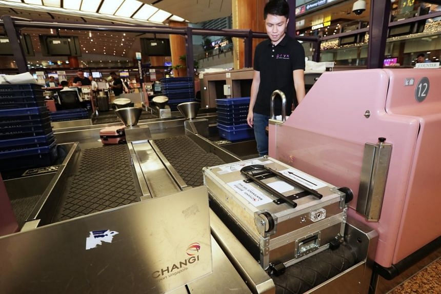 Staff demonstrates the Smart Luggage retrofitted with cameras and sensors to detect anomalies in the conveyor system as it is transported through Changi Airport's Baggage Handling System.