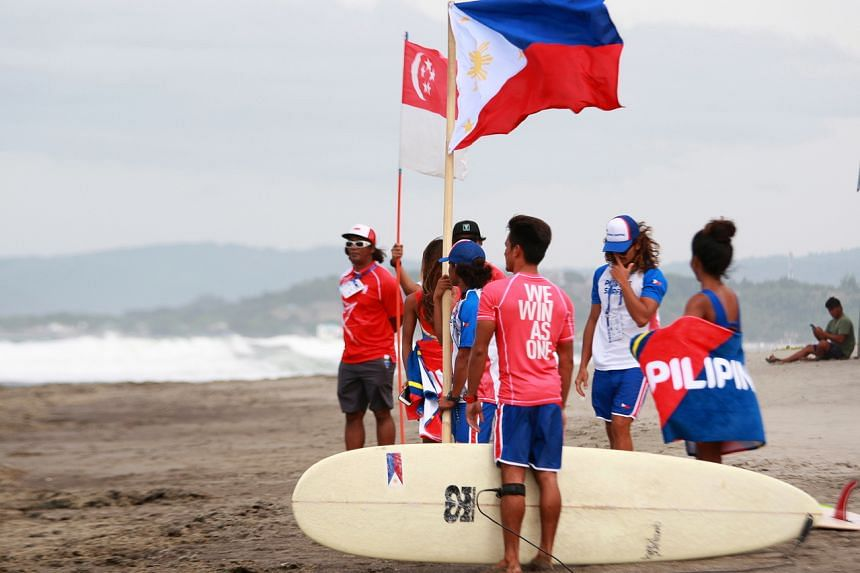 Filipino and Singaporean surfing team members during the Surfing events of the Southeast Asian Games in San Juan, La Union province, Philippines on Dec 2, 2019.