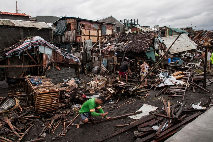 Villagers work among damaged houses in the aftermath of Typhoon Kammuri in Legazpi, the Philippines, on Dec 3, 2019.