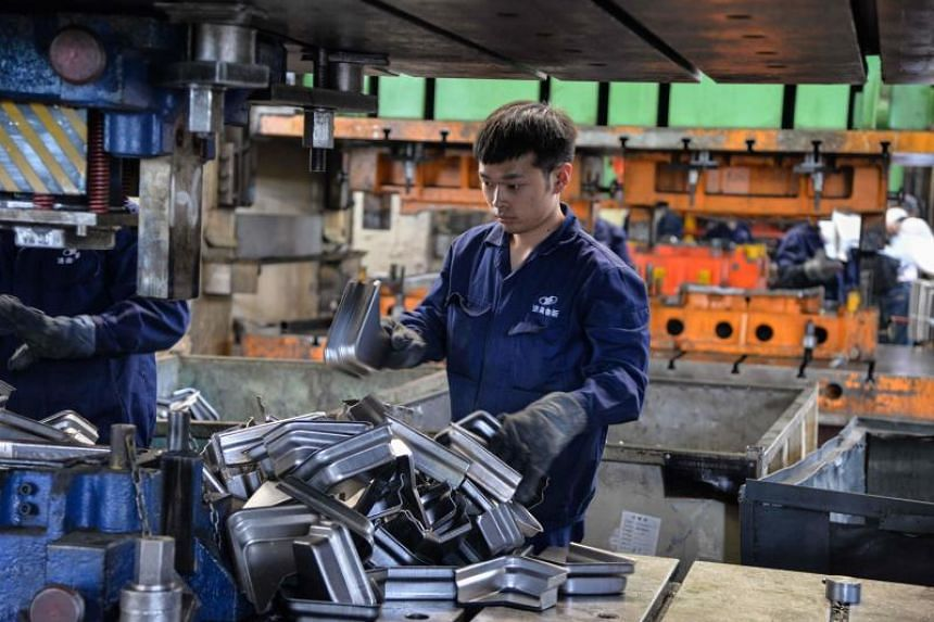 A Chinese employee works on vehicle parts at a factory in Jinan, China, on May 11, 2019.