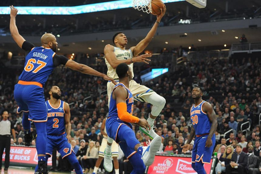 Milwaukee Bucks player Giannis Antetokounmpo (in white) lays up a shot during the game against the New York Knicks on Dec 2, 2019.