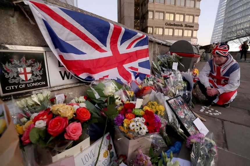 A man lights candles in front of placards and tributes to victims on London Bridge.