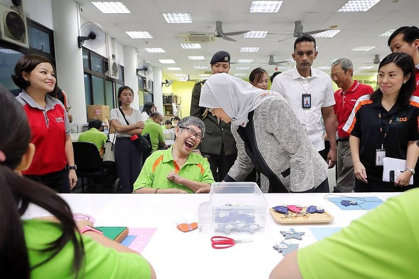 President Halimah Yacob with SPD trainee Lay Choo at the Sheltered Workshop in the SPD Ability Centre in Tiong Bahru yesterday. Also present was Keppel chairman Lee Boon Yang (right).