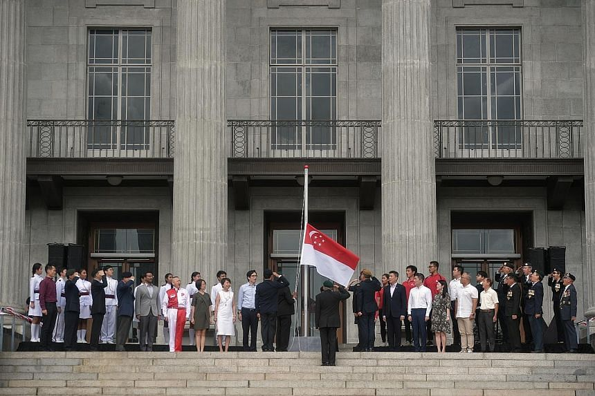 Members of the Singapore Armed Forces Veterans' League saluting during the flag-raising ceremony and singing of the National Anthem at the 60th anniversary commemoration of the national symbols yesterday at the National Gallery Singapore.