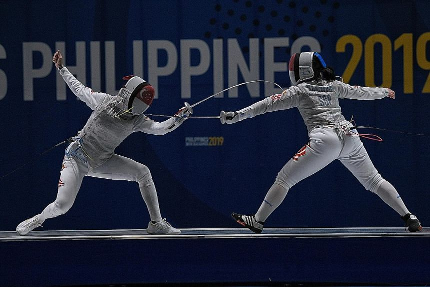 Amita Berthier (left) en route to defeating teammate Maxine Wong in the women's foil final yesterday to retain her gold. After receiving treatment for an ankle injury, she recovered from 10-9 down to win 15-10. ST PHOTO: MARK CHEONG
