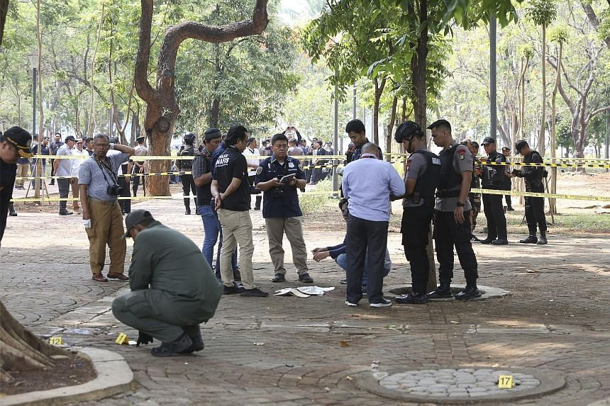 Investigators at the site of an explosion near the presidential palace in Jakarta, Indonesia's capital, yesterday. PHOTO: ASSOCIATED PRESS
