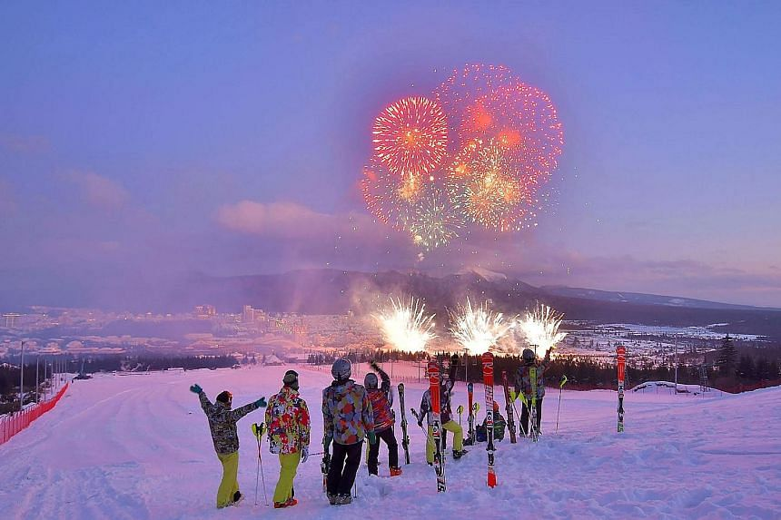 """Skiers watching fireworks during a ceremony to mark the completion of the township of Samjiyon county in North Korea on Monday. The city is envisaged as a """"socialist utopia"""" with new apartments, hotels, a ski resort and commercial, cultural and medic"""