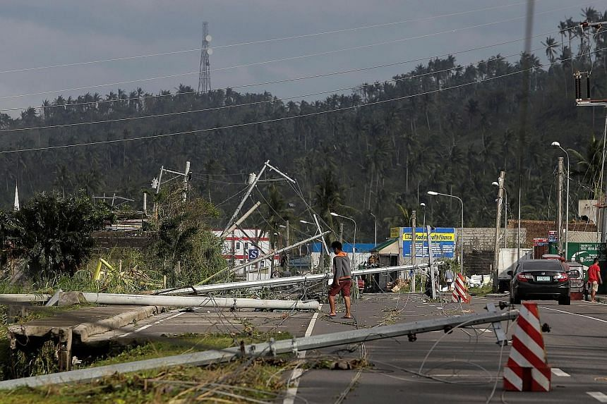 A man walking past fallen electric poles on the main highway after Typhoon Kammuri hit Camalig town in the Philippines yesterday. PHOTO: REUTERS Villagers working among damaged houses in the aftermath of Typhoon Kammuri in Legazpi city, the Philippin