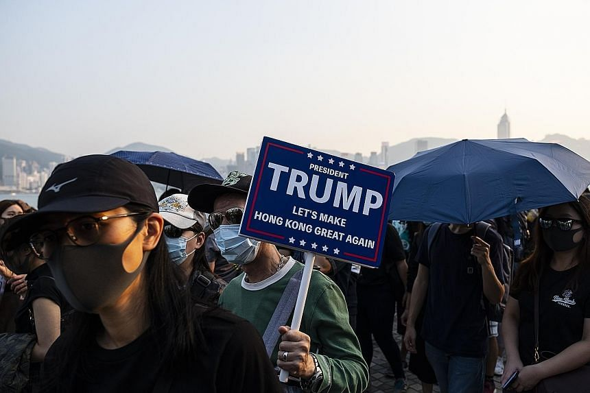 A demonstrator with a placard in support of US President Donald Trump during a protest in the Tsim Sha Tsui district of Hong Kong on Sunday. The city has been rocked by months of protests that were sometimes violent. They were sparked by a now-withdr
