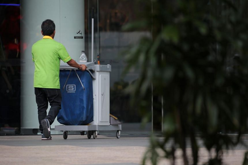 A cleaner pushes his trolley outside Dhoby Ghaut MRT on Oct 31, 2019.