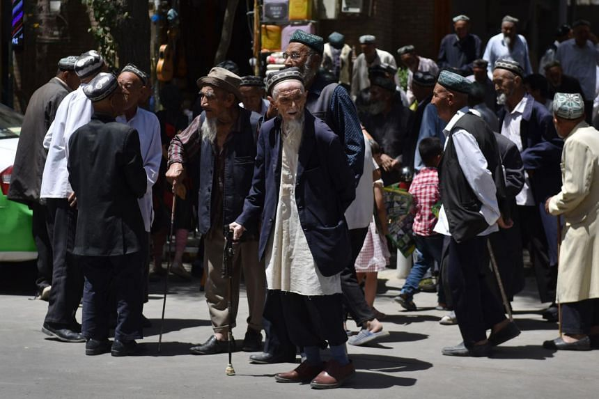 In a photo taken on May 31, 2019, Uighur men are seen leaving a mosque after prayers in Hotan, China's north-west Xinjiang region.