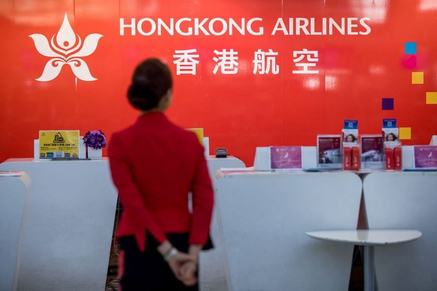 A Hong Kong Airlines staff member stands at the departure hall of the Hong Kong International Airport on Dec 3, 2019.