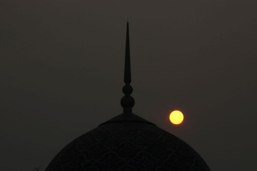 In a photo taken on Sept 17, 2019, the sun sets above a mosque on a hazy day in Putrajaya, Malaysia.