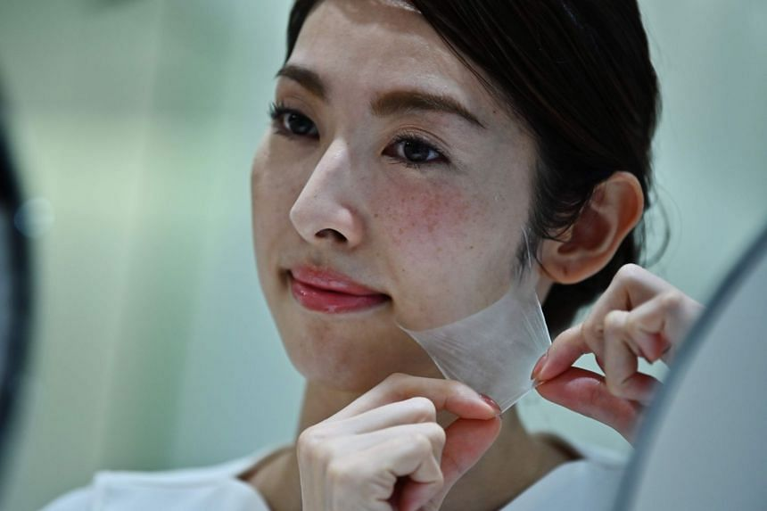An employee for Japanese cosmetics company Kao removes a super thin transparent layer after using a palm-sized diffuser on her face, during a product demonstration in Tokyo on Dec 4, 2019.