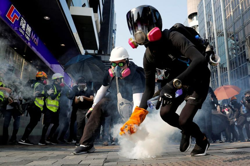 In a photo taken on Oct 20, 2019, an anti-government protester holds a tear gas canister during a protest in Hong Kong.