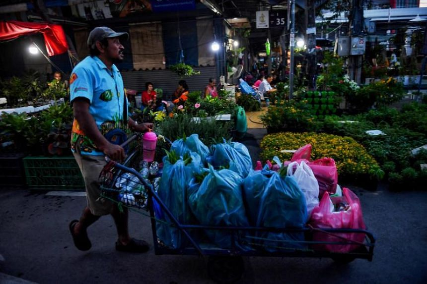 In this photo taken on Oct 29, 2019, a man carries plants on a cart at an outdoor flower market in Bangkok.