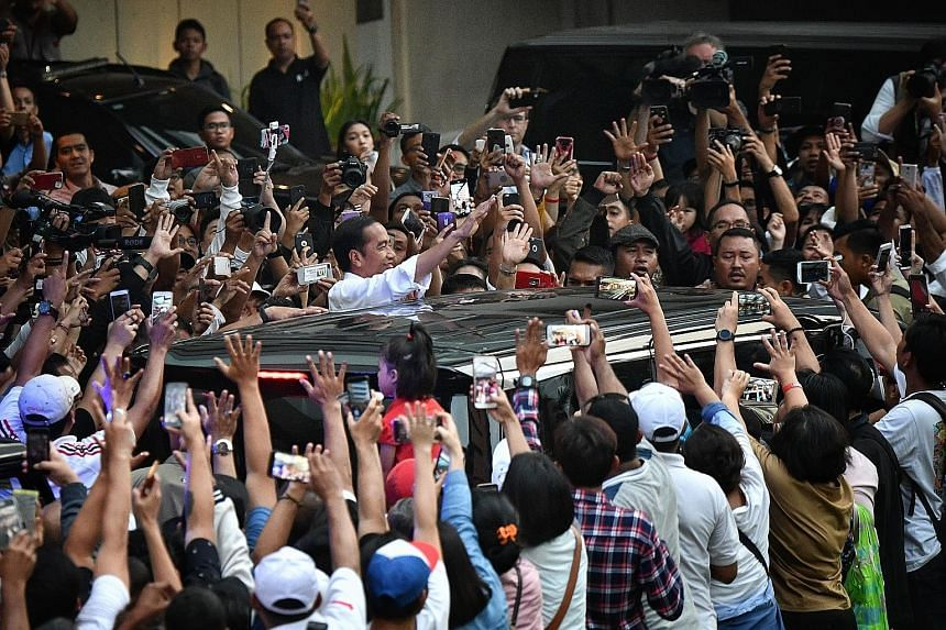 A crowd of supporters cheering Mr Joko Widodo in Jakarta after the presidential election in April. He defeated retired army general Prabowo Subianto to retain power for a second and final term in office in the world's largest Muslim-majority country