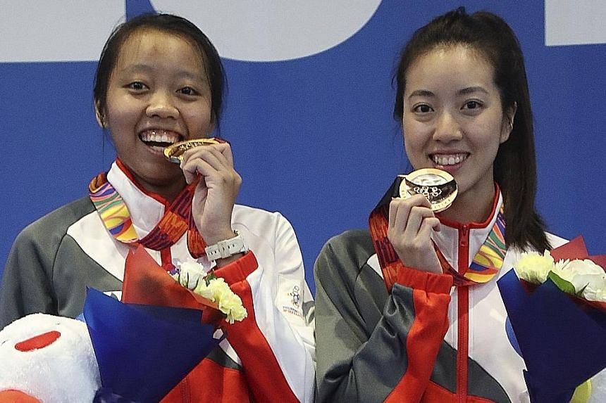 Women's epee champion Kiria Tikanah Abdul Rahman (far left) with bronze medallist Cheryl Lim, whom she beat 15-10 in the semi-finals. Joshua Lim also won a bronze, in the men's foil.