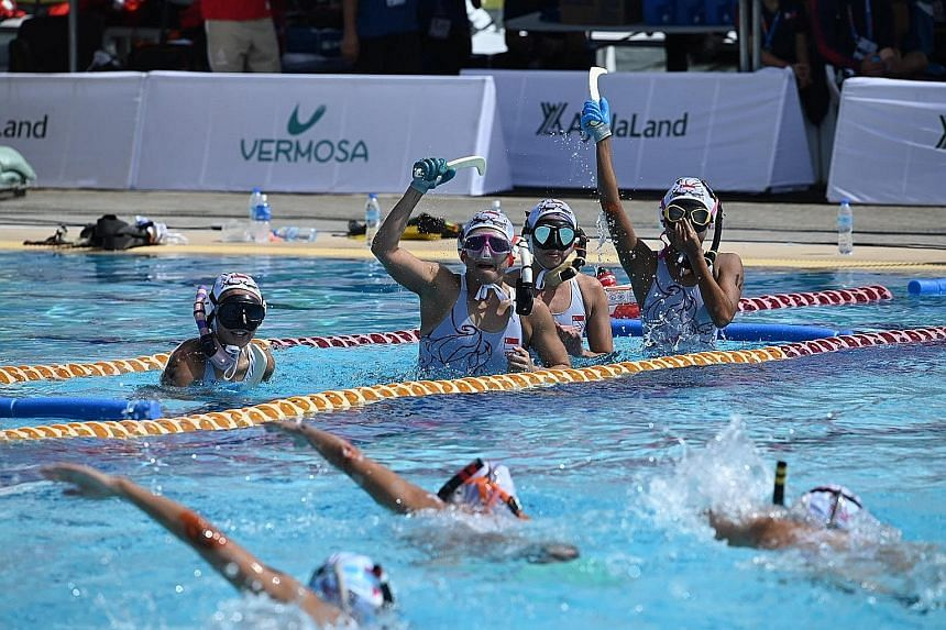The Singapore women's team raising their sticks in celebration during the 4x4 underwater hockey final against the Philippines, which they won 4-2. PHOTO: LIANHE ZAOBAO