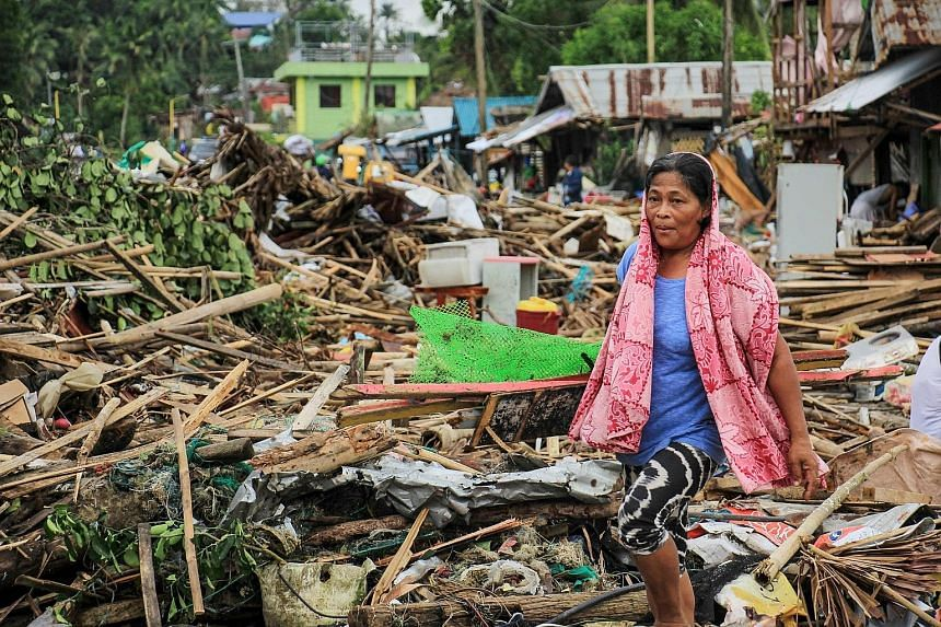 A resident surrounded by debris in the wake of Typhoon Kammuri in the city of Sorsogon, south of Manila, on Tuesday. Typhoon Kammuri made landfall on Monday night, prompting the forced evacuation of thousands of residents and the cancellation of hund