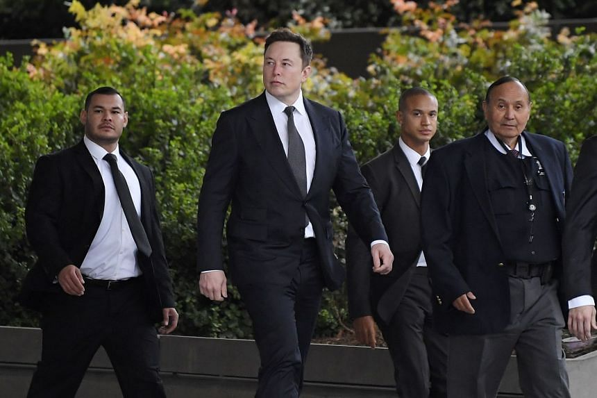 Musk (second from left) arrives at the US District Court in Los Angeles.