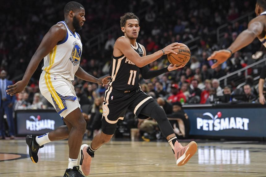 Atlanta Hawks guard Trae Young (right) runs past Golden State Warriors forward Eric Paschall during the second half of their game at State Farm Arena in Atlanta, Georgia.