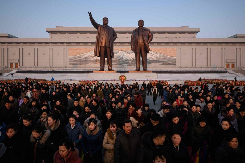 In a photo taken on Feb 16, 2019, an image of Mount Paektu is displayed behind the statues of late North Korean leaders Kim Il Sung and Kim Jong Il, as people pay their respects on Mansu hill in Pyongyang.