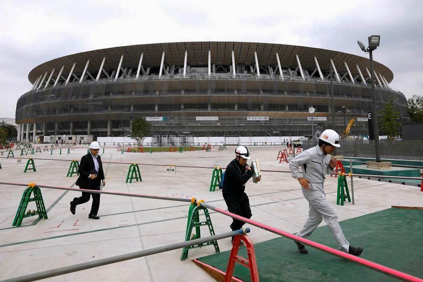 Workers are seen at the construction site of the main stadium for the Tokyo 2020 Olympics and Paralympics on July 3, 2019.