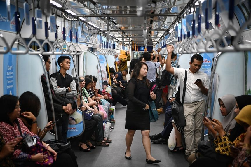 A photo from April 1, 2019, shows commuters on a Jakarta subway train.