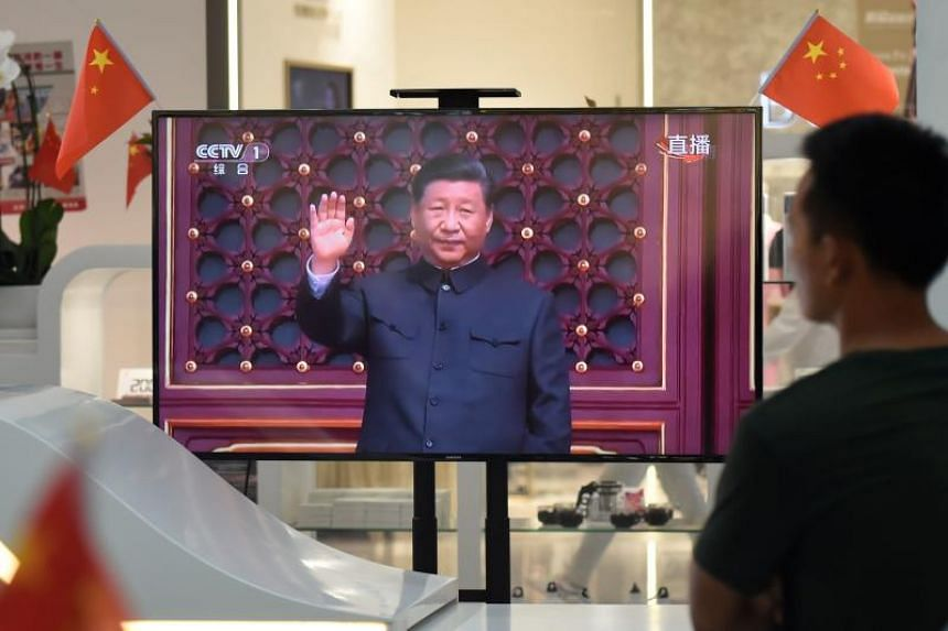 A photo taken on Oct 1, 2019, shows a repeat broadcast of a military parade at Tiananmen Square, to mark the 70th anniversary of the founding of the People's Republic of China, at a mall in Beijing.