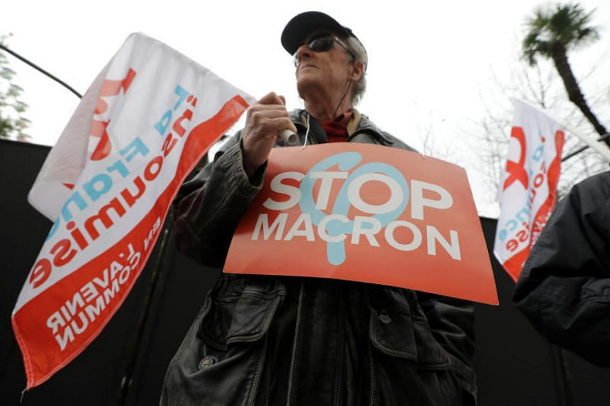 """A protester holds a placard that reads """"Stop Macron"""" during a demonstration against the French government's pension reform plans in Nice as part of a national strike and day of protests in France, on Dec 5, 2019."""