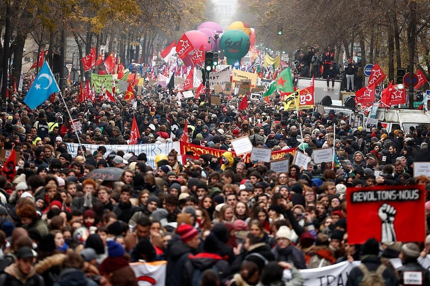 Protesters gathering for a demonstration in Paris yesterday against the French government's pension reform plan. The Eiffel Tower was forced to shut down, while France's vaunted high-speed trains stood still and metro stations across Paris shut their